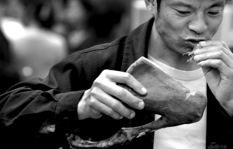 A Chinese man eating dog meat.