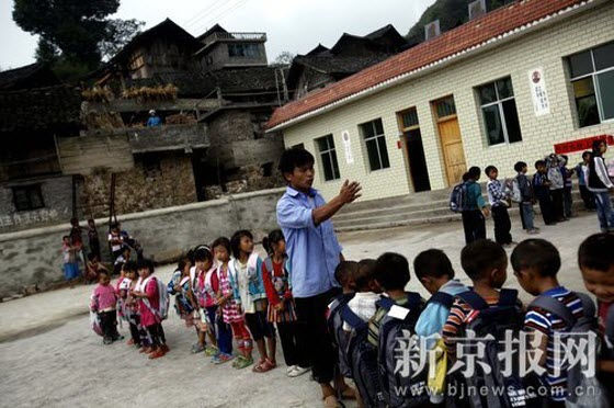 September 4th, substitute teacher Pan Dejiang is lining up the kids to get new schoolbags. Behind him are the 3 classrooms and one teacher's office that he and Pan Delu personally went to the county government to apply for over 20 times before finally getting it built in 2008 after finding a kind Hong Kong donor who donated 50,000 yuan.