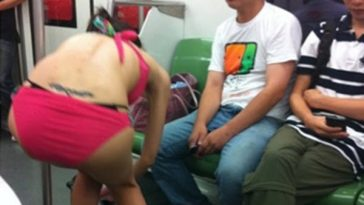 A girl changing her outfit in public on the Shanghai Metro.