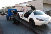 A white Mercedes Benz SLS being carried away on a flat-bed truck after its young Chinese owner was caught street racing in Surrey, Canada.