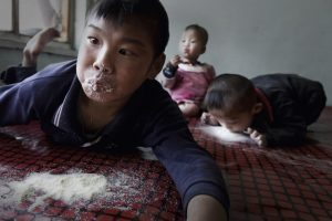 A Chinese child with cerebral palsy licks milk powder off a bed to feed.