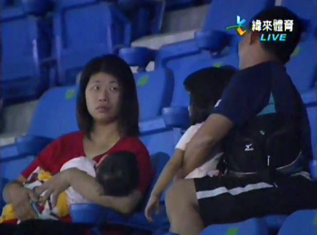 In Taiwan, a wife glares at her husband at a baseball game after he dropped their daughter in a rush to catch a foul ball.