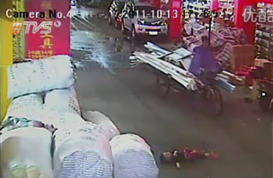 A Chinese man riding by on his tricycle cart carrying pipes, avoiding the body of a 2-year-old little girl on the road.