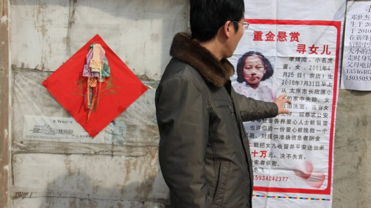 A man stands in front of a poster for a missing child in China.