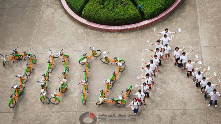 "A group of Chinese spell out the Chinese words for ""7 billion people""."