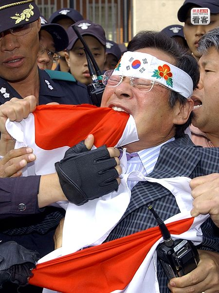 A Korean man tears apart a Japanese national flag with his teeth to protest Prime Minister Junichiro Koizumi's 5th consecutive visit to the Yasukuni Shrine.