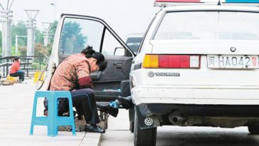 A photograph of a Chinese police officer having his shoes cleaned, polished, and shined at the side of the road incites heated online discussions amongst Chinese netizens.