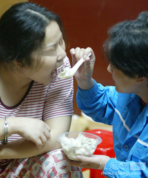 A fellow inmate feeds He Xiuling some dumplings as a late night snack, on the eve of her execution for drug trafficking crimes.