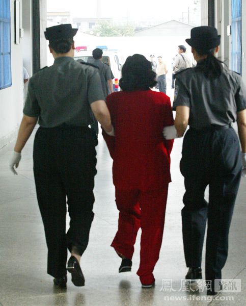 Chinese female prison guards escorting a condemned prisoner to her execution.