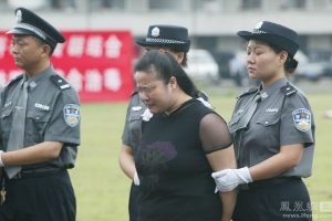 A Chinese woman sentenced to death is escorted by guards to her execution.
