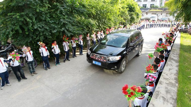 Primary schoolchildren in Fujian province line the street with flowers in hand to welcome government officials attenting a Buddhism seminar.