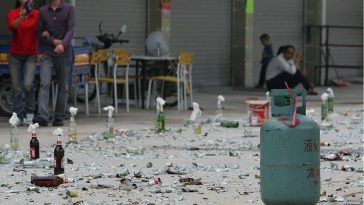 Broken glass, molotov cocktails, and propane tanks scattered across a village street in Guangzhou by residents trying to block a government demolition of illegal buildings in the village.
