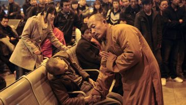 A monk prays for a dead elderly man discovered by other travelers in a Shanxi, China train station.