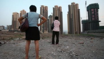 Two Chinese women looking at apartment buildings under construction in Chongqing.