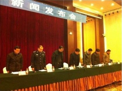 Local government officials and police bowing at a press conference for the Jiangsu Xuzhou Feng County school bus rolling over accident that has so far resulted in 15 deaths.