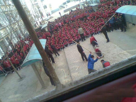 Students of a martial arts school in Henan, China are gathered to watch some students being disciplined by teachers and trainers.