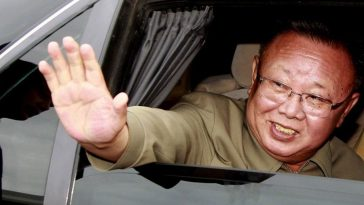 Kim Jong-il waves out a car window.