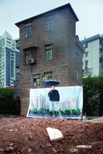 A former resident of Yangjicun standing in front of his old home with a poster of the future redeveloped Yangjicun.