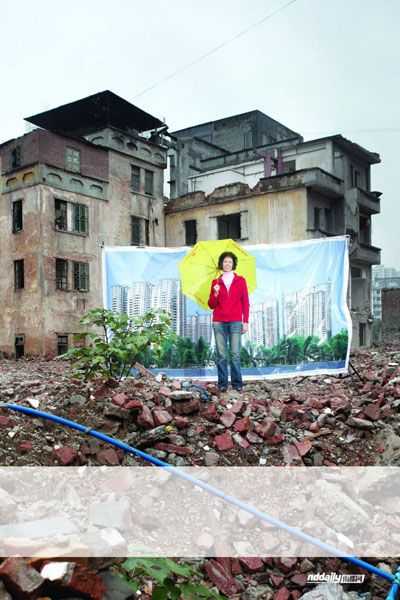 A former resident of Yangjicun standing in front of her old home with a poster of the future redeveloped Yangjicun.
