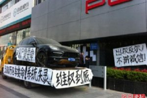 A black Porsche Cayenne SUV on a flatbed truck with banners hung on it by its owner who claims it has serious quality and safety problems and wants a refund from Porsche.