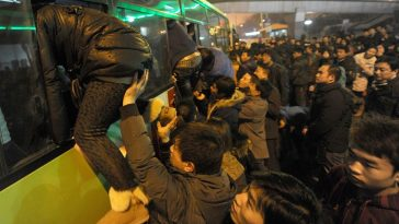 Bus riders in Beijing, China crawling through the windows to get onto a crowded public bus during rush hour.