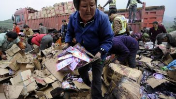 Local villagers in Qijiang county of Chongqing rush to loot spilled laundry detergent goods scattered on the highway after a cargo truck accident.