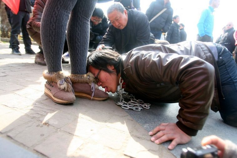 Kang Yi licks the shoe of a woman, while wearing a chain link collar and leash, in a performance art in Wuhan promoting respect for women.
