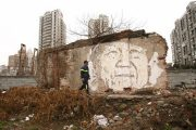 An engraved portrait of a Chinese head of household on a home that is about to be demolished in Shanghai, by Portugese graffiti artist Vhils.