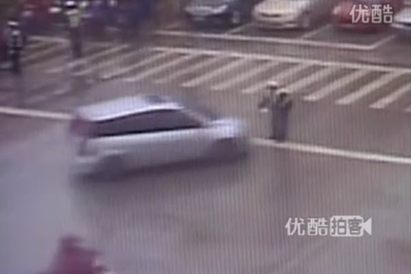 Absent-minded Chinese driver trying to pass other cars while making a left turn accidentally hits traffic officer, sending the man flying.
