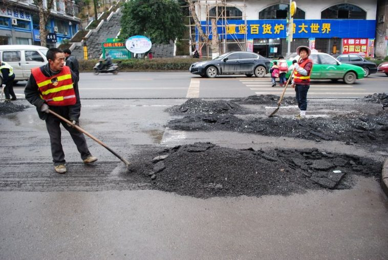 Construction workers repaving recently paved roads in Kaili city of Guizhou province in China.
