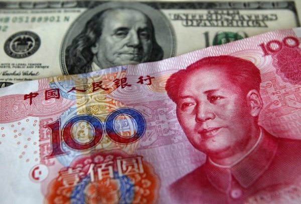 100 USD banknote next to 100 RMB banknote.