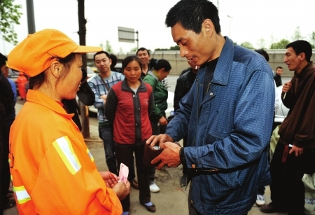 Truck driver Wang Hongjun gives a cash reward to a sanitation worker who returned a box of cargo that had fallen off of Wang's truck.