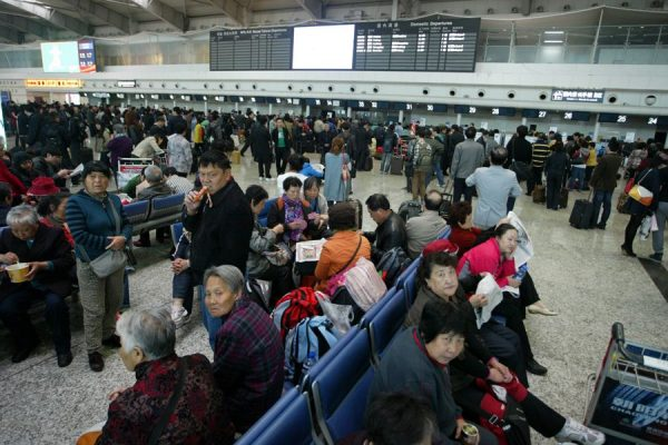 Crowds of delayed airline passengers grounded at Dalian Airport due to foggy weather conditions.