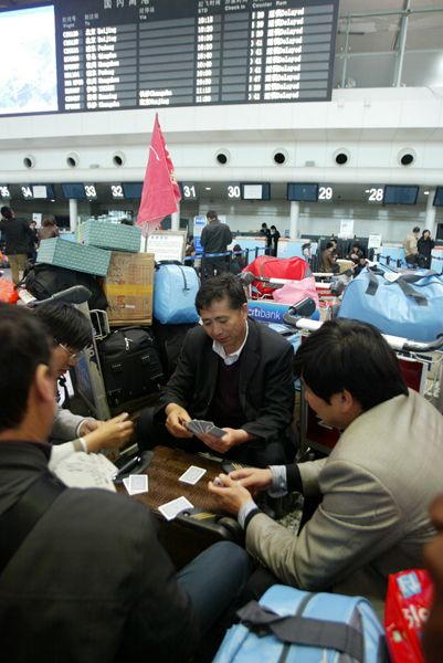 A group of delayed airline passengers playing card games to pass the time while being grounded at Dalian Airport due to foggy weather conditions.