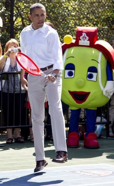 Obama is gripping the racket with his left hand.