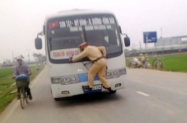 Vietnamese traffic officer Lt. Nguyen Manh Phan clutching to the front of a speeding bus.