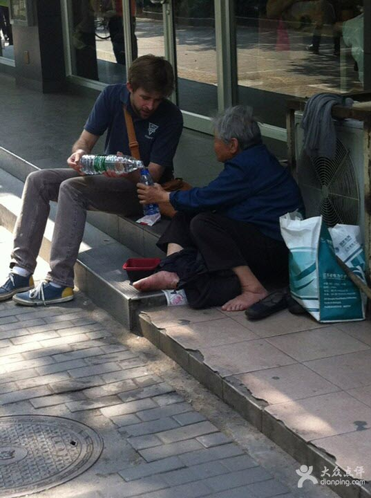 A young American man pours water for an old beggar in Nanjing, chatting and sharing fries from McDonald's with her.