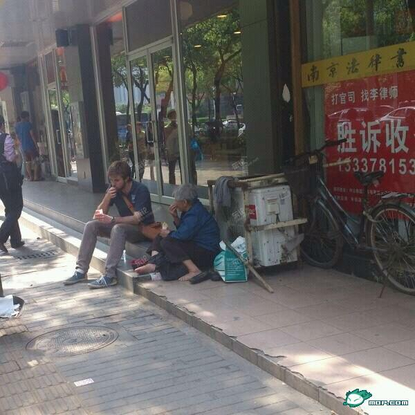 An American young man sits and chats with an old Chinese beggar in Nanjing, sharing some McDonald's fries with her.