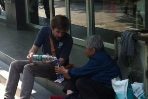 An American young man sits and chats with an old Chinese beggar in Nanjing.