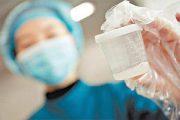 An Asian nurse in blue holds up a bottle of donated semen sperm.