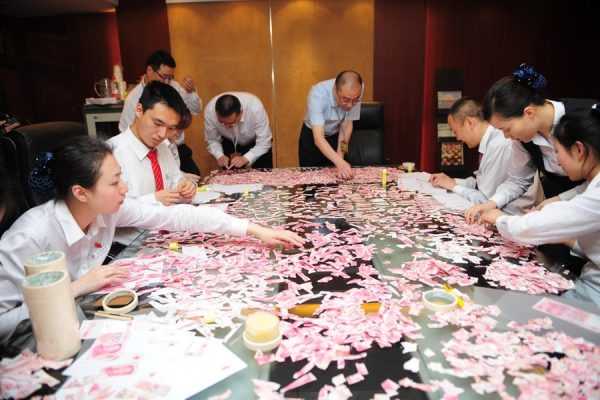 12 Chinese bank workers attempting to piece back together 50k RMB worth of cash that had been torn up by a man's wife.