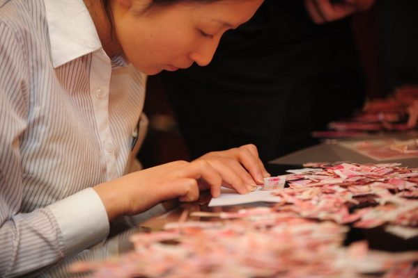 A Chinese female bank worker attempting to piece together 50k RMB worth of Chinese money torn into strips and pieces.