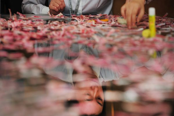 A male Bank of China employee attempting to piece back together over 50k worth of 100 RMB bills that had been torn to pieces by a man's sick wife..