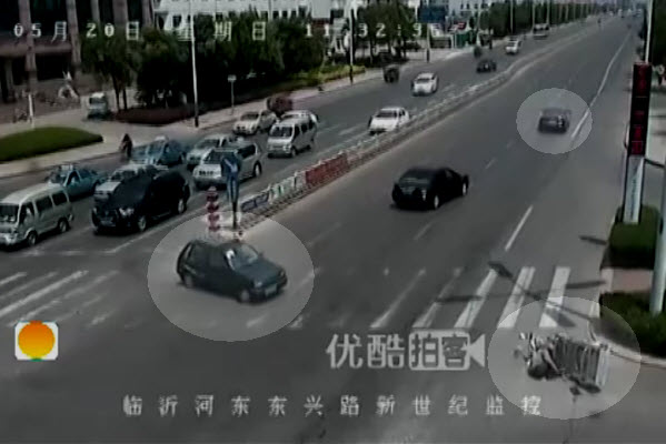 A young man in a small hatchback making a U-turn happens to see the old man on the ground, while the black Audi drives away.