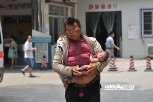 A mentally ill homeless Chinese woman carrying her naked newborn baby on the streets of Guangzhou.