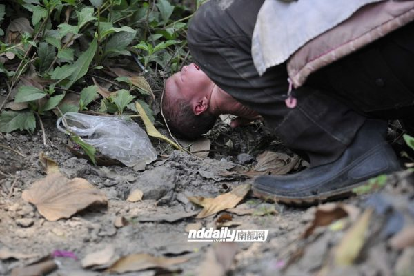 The mentally ill homeless Chinese woman's baby lies naked on the ground crying as she drinks water from a roadside drainage ditch.