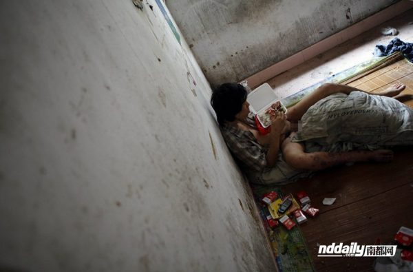Wu Guilin, a drug addict in Guangdong province of China, lies half naked against the wall of his dilapidated home.