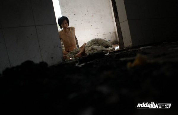 Wu Guilin, a drug addict in Guangdong province of China, shirtless and gaunt inside his dilapidated home.