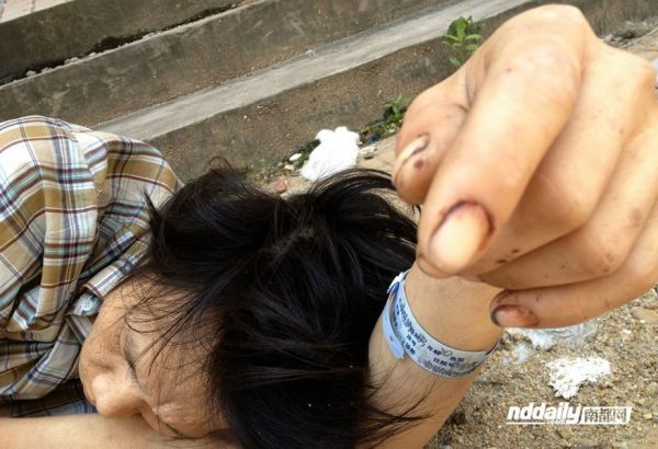 Chinese drug addict Wu Guilin found on the street next to an abandoned building, his body too weak to walk.