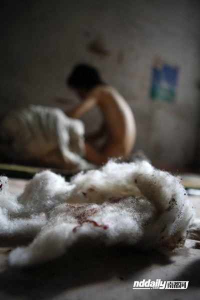 Cotton wadding with traces of blood litter Wu Guilin's filthy home.